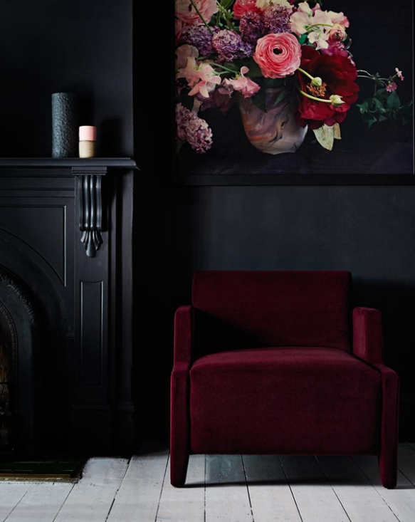 saturated red chair with black walls & fireplace